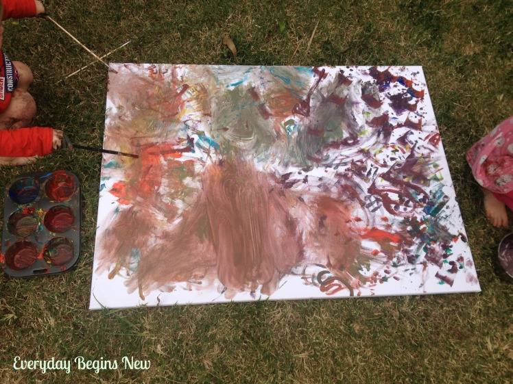 toddler painting using paint brushes