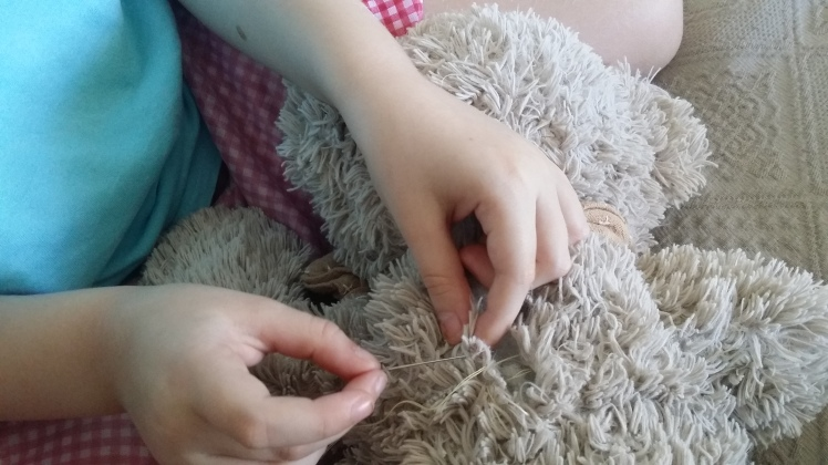 mending her teddy at 5 years